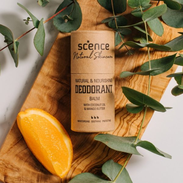 Summer citrus deodorant on wooden board with green foliage and a slice of orange.