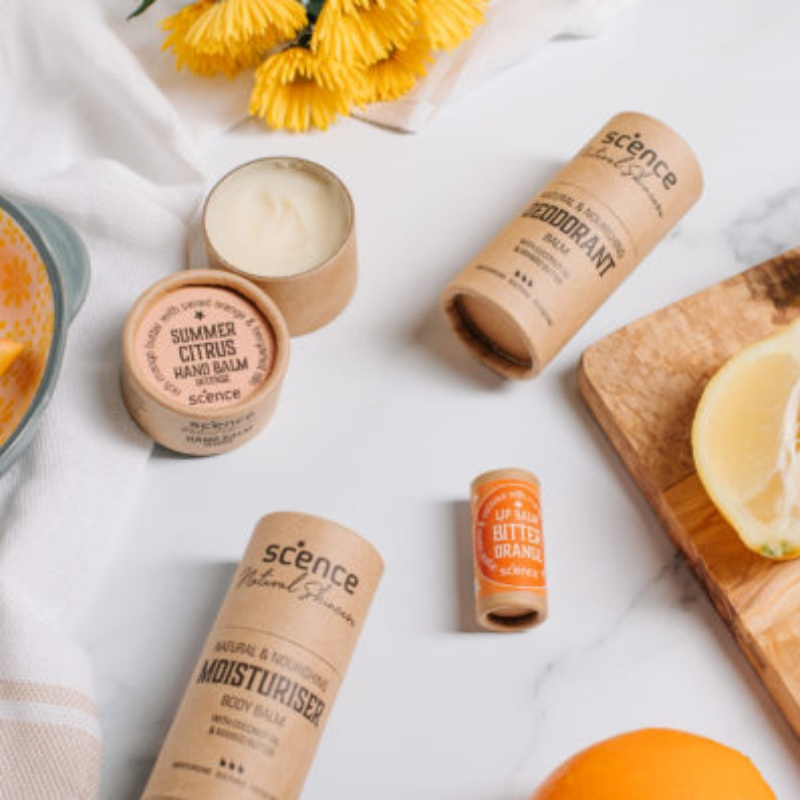 Bitter Orange Lip Balm by Scence on a white background with hand balm and deodorant