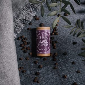 Black Peppery Lip Balm by Scence on grey background with peppermint corns
