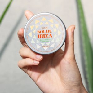 Sol de Ibiza in persons hand with aloe vera background